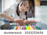 asian girl playing color pencil ... | Shutterstock . vector #1033253656
