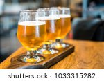 3 cups of draft been on wooden... | Shutterstock . vector #1033315282