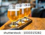3 cups of draft been on wooden... | Shutterstock . vector #1033315282