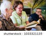 nurse reading book to elderly... | Shutterstock . vector #1033321135