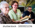 nurse reading book to elderly... | Shutterstock . vector #1033321156
