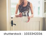 a young woman is standing by a... | Shutterstock . vector #1033342036