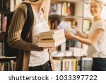 close view of book stack held... | Shutterstock . vector #1033397722