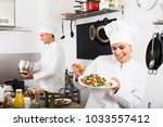 laughing female cook wearing...   Shutterstock . vector #1033557412