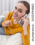 Small photo of Pleasant chat. Positive jolly jovial woman chatting on phone while smiling and gazing at camera