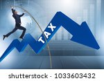 businessman jumping over tax in ... | Shutterstock . vector #1033603432