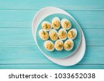 stuffed eggs on blue plate for... | Shutterstock . vector #1033652038