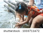 asian child girl playing water... | Shutterstock . vector #1033711672