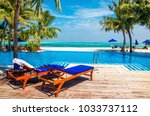 wooden deck chairs with blue... | Shutterstock . vector #1033737112