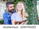 Small photo of Girl with happy face fall in love with bearded man, couple reads poems. Romantic couple holds old book with poems. Date and love concept. Couple in love sits and hugs outdoor, nature background.