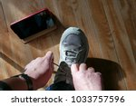 Small photo of Tucson, Arizona, USA, February 13: Woman tying shoelace of sneakers with iPhone next to foot on wooden floor