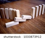 Small photo of Photo of light beige wooden bricks arranged in a row like a domino row, with some of the bricks lying on the floor. Construction concept. Failure concept.