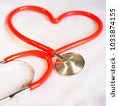 a stethoscope shaping a heart... | Shutterstock . vector #1033874155