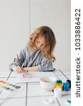 little girl painting with... | Shutterstock . vector #1033886422