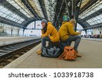 bored couple sit on their bags... | Shutterstock . vector #1033918738