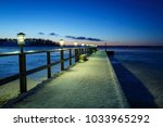 jetty with snow and lights at... | Shutterstock . vector #1033965292