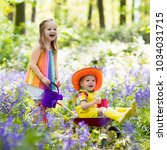 kids with bluebell flowers ... | Shutterstock . vector #1034031715