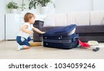 toddler boy packing things in...   Shutterstock . vector #1034059246