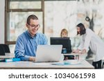 intern at the office working on ... | Shutterstock . vector #1034061598
