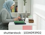 young muslim girl wotking on... | Shutterstock . vector #1034093902