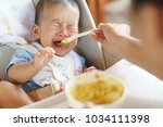 6 months old asian baby refuse... | Shutterstock . vector #1034111398
