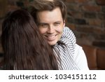 Small photo of Young sly liar man happily smiling while woman embracing him, dishonest cheating boyfriend womanizer hiding grin hugging naive girlfriend, insincere husband deceiving wife showing fake feelings