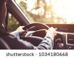 woman driving car at sunset. | Shutterstock . vector #1034180668