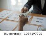 men's hands  sending money to... | Shutterstock . vector #1034197702