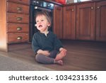a sad little toddler is sitting ... | Shutterstock . vector #1034231356