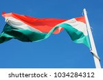 colored flag of hungary on sky... | Shutterstock . vector #1034284312