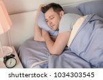 young man sleeping in bed at... | Shutterstock . vector #1034303545