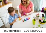 mother with kid painting easter ... | Shutterstock . vector #1034369026