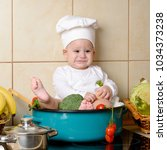 adorable baby boy in kitchen | Shutterstock . vector #1034373238