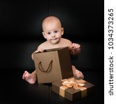 baby boy unpacking surprise box | Shutterstock . vector #1034373265