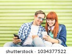 Stock photo happy young couple having fun with mobile smart phone at vintage grunge location friendship 1034377522
