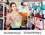 Stock photo positive cheerful smiling girl looking for cage for small pet in shop 1034390962