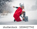 Small photo of Young woman in image of Germanic-Scandinavian God of thunder and storm are striking with hammer in fury against winter forest background. Cosplay.