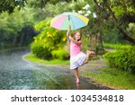 kid playing out in the rain.... | Shutterstock . vector #1034534818