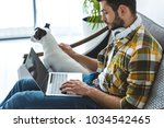Stock photo bearded man using laptop while sitting on sofa with dog 1034542465