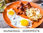 Small photo of Closeup of large breakfast brunch plate with fried eggs, hash browns shredded potatoes, sausage tako octopus, yellow drink