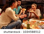 young people having pizza party ... | Shutterstock . vector #1034588512