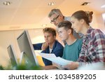 students in class with teacher... | Shutterstock . vector #1034589205