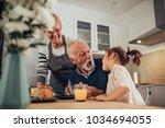 grandparents having breakfast... | Shutterstock . vector #1034694055
