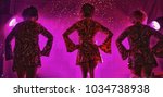 Small photo of trio of female performers on stage about to begin their act