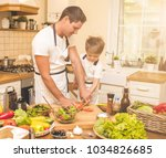 father is cooking with his son | Shutterstock . vector #1034826685