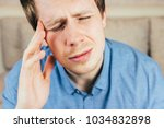 young man holding his head... | Shutterstock . vector #1034832898