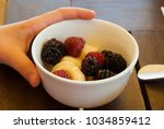 plate with red berries ... | Shutterstock . vector #1034859412