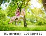 two cute little sisters having... | Shutterstock . vector #1034884582