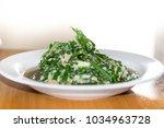 stir in green vegetables in a... | Shutterstock . vector #1034963728