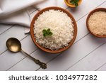 Small photo of Cooked plain white basmati rice in terracotta bowl over plain or wooden background